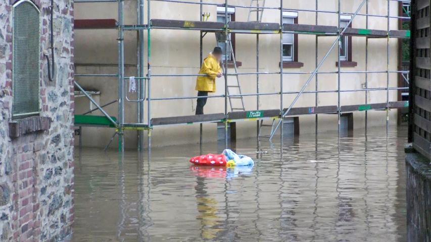 Ein Mann betrachtet die geflutete Straße unter ihm.