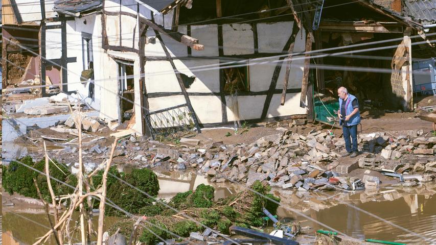 Ein Mann begutachtet das Chaos im Dorf Schuld im Kreis Ahrweiler.