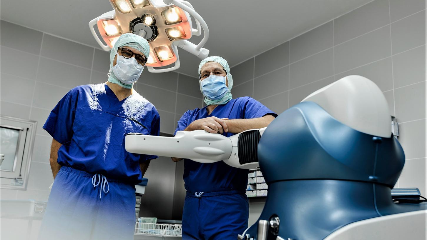 Die beiden Fachärzte Chefarzt Dr. med. Mathias Bender (rechts) sowie Oberarzt Dr. Nikolaj Vasak mit dem OP-Roboter im Operationsaal.