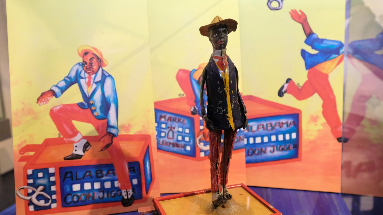 Die beanstandete Blechfigur von 1912 und die moderne Interpretation auf den plakativen Bildern im Hintergrund: Der Schwarze zieht den Schlüssel ab, der ihn zum Tanzen zwingt, wirft ihn weg und verlässt das Podium.