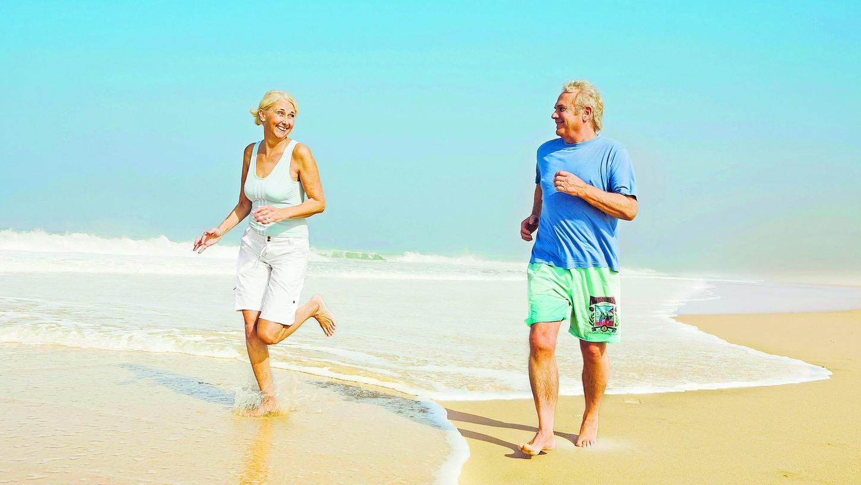 Wer regelmäßig, aber nicht übertrieben Sport treibt, erhöht die Wahrscheinlichkeit, im Alter noch Sex haben zu können. Dieses Paar wirft sich bei einer gemeinsamen Joggingrunde am Strand verliebte Blicke zu.