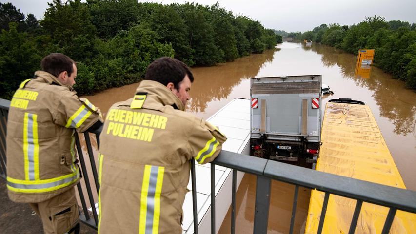 Die B265 bei Erftstadt ist völlig überflutet. Feuerwehrmänner blicken auf ineinander verkeilte LKWs.