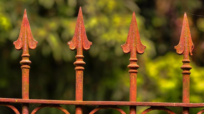 Mit Rost erst richtig schön: Zaunausschnitt aus einer recht alten Schmiedeeisernen Garteneinfriedung.