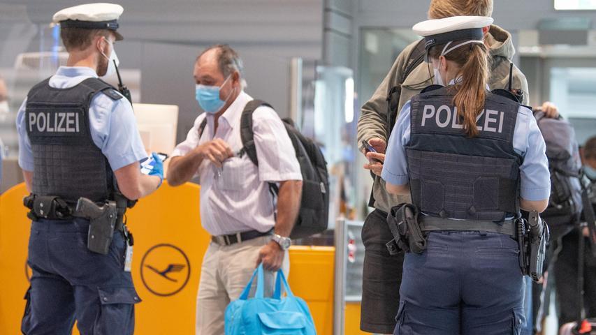 Bundespolizisten kontrollieren an den Flughäfen die Dokumente der Passagiere aus den Urlaubsländern. Negative PCR-Tests und Impfausweise müssen vorliegen.