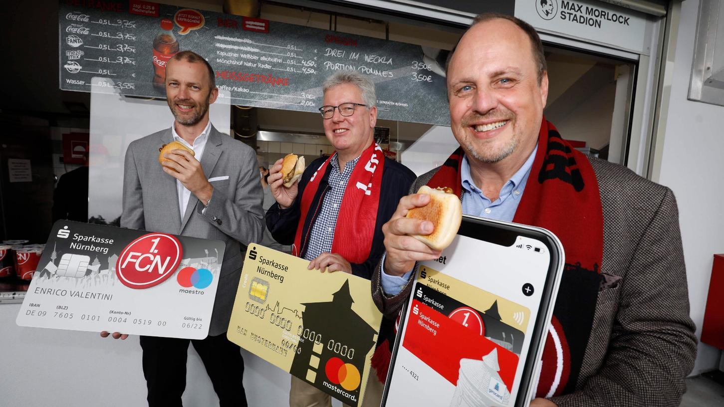 Die erste mobile bezahlte Bratwurst ging am Samstag beim Club über den Tresen - Niels Rossow vom 1. FC Nürnberg, Matthias Everding von der Sparkasse und Bürgermeister ChristianVogel (vonlinks) ließen es sich schmecken.