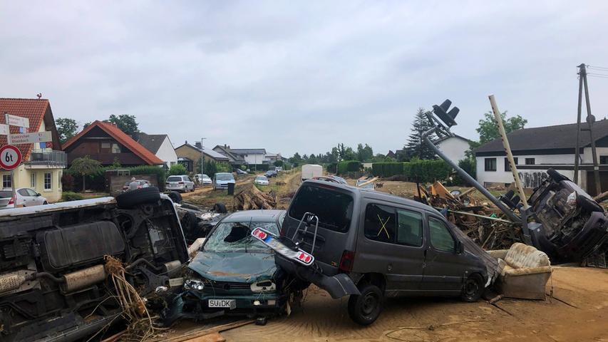 Zerstörte Autos liegen an einem Bahnübergang in Swisttal-Odendorf Rhein-Sieg-Kreis. Sie wurden mitgerissen, als der Orbach über die Ufer trat und eine Flutwelle durch die Dörfer strömte.
