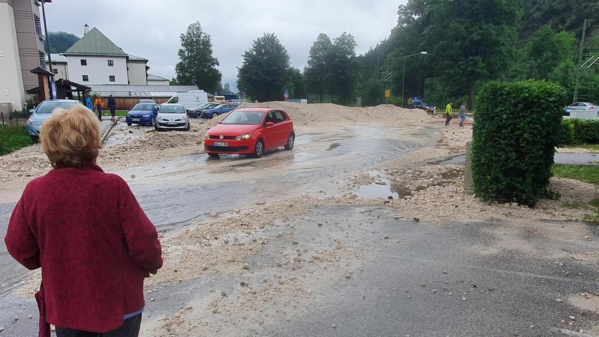 Bischofswiesen: Eine Frau beobachtet wie ein Auto überdie überspülte Straße fährt.