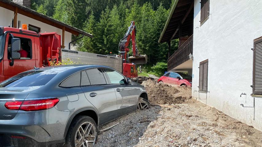 In Schönau am Königssee begannen am Montagmorgen die Aufräumarbeiten. Ein Murenabgang hat hier ein Grundstück mit Schlamm und Geröll bedeckt, samt geparkten Autos.