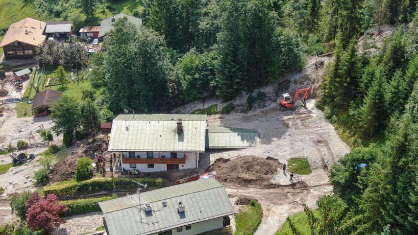 Luftaufnahmen zeigen, wie ein Murenabgang ein ganzes Anwesen zerstört hat.