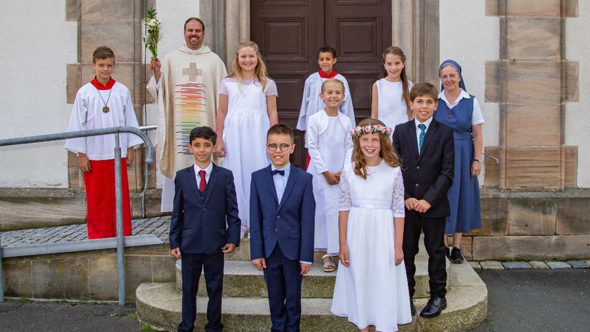 Die Erstkommunionkinder stellten sich vor dem Gottesdienst zur feierlichen Prozession auf und zogen mit ihren Kerzen in die Kirche. Diese wurden von Pfarrer Saffer angezündet