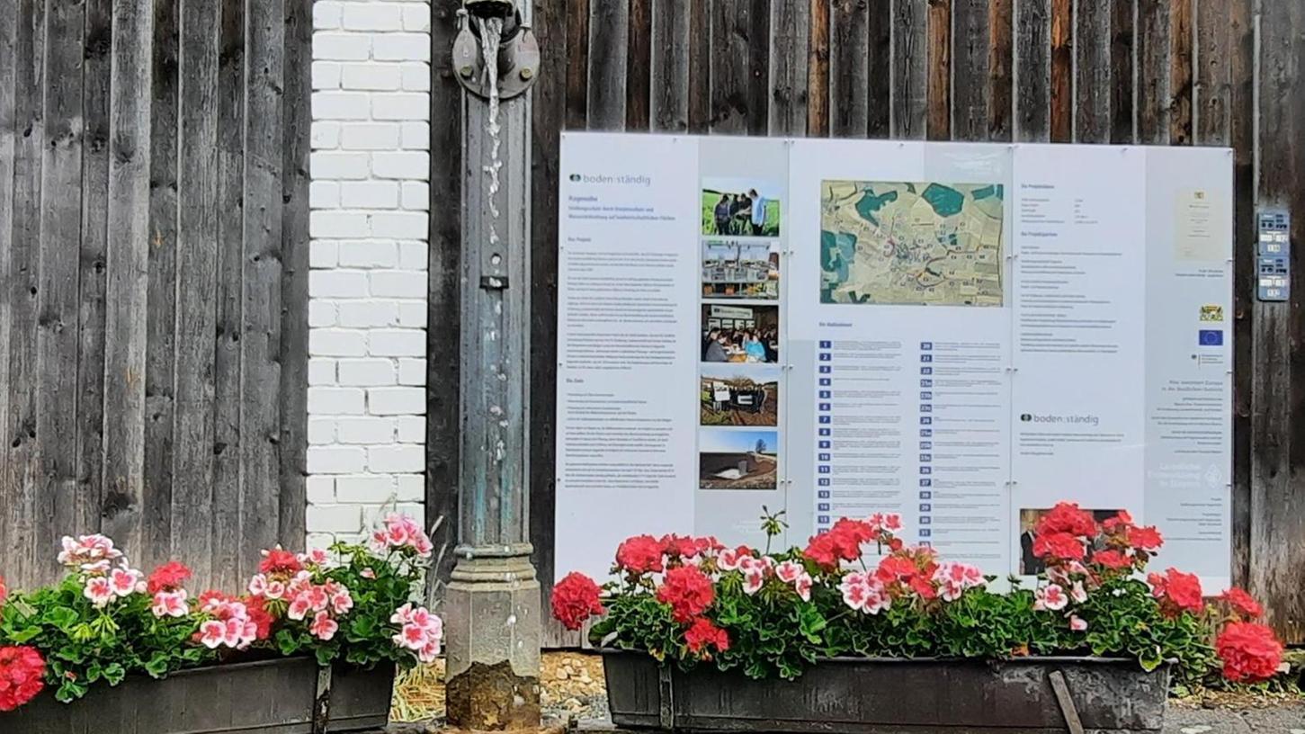 """Eine große Beschreibung an der Scheunenwand hinter dem Dorfbrunnen erinnert im Ortsteil Hagenohe an das laufende Projekt """"boden:ständig""""."""