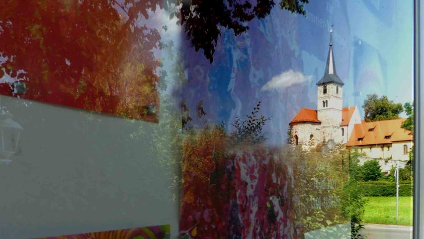 """Kunst über Jahrhunderte verbindet das Spiegelbild des imposanten Münsters in einer einladenden Bildtafel am Münchsteinacher """"Strack-Haus"""".  Foto:o.n."""