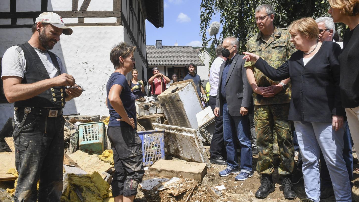 Bundeskanzlerin Angela Merkel und Malu Dreyer,Ministerpräsidentin von Rheinland-Pfalz, sprechen mit betroffenen Anwohner bei ihrer Besichtigung des vom Hochwasser verwüsteten Dorfs Schuld bei Bad Neuenahr-Ahrweiler.
