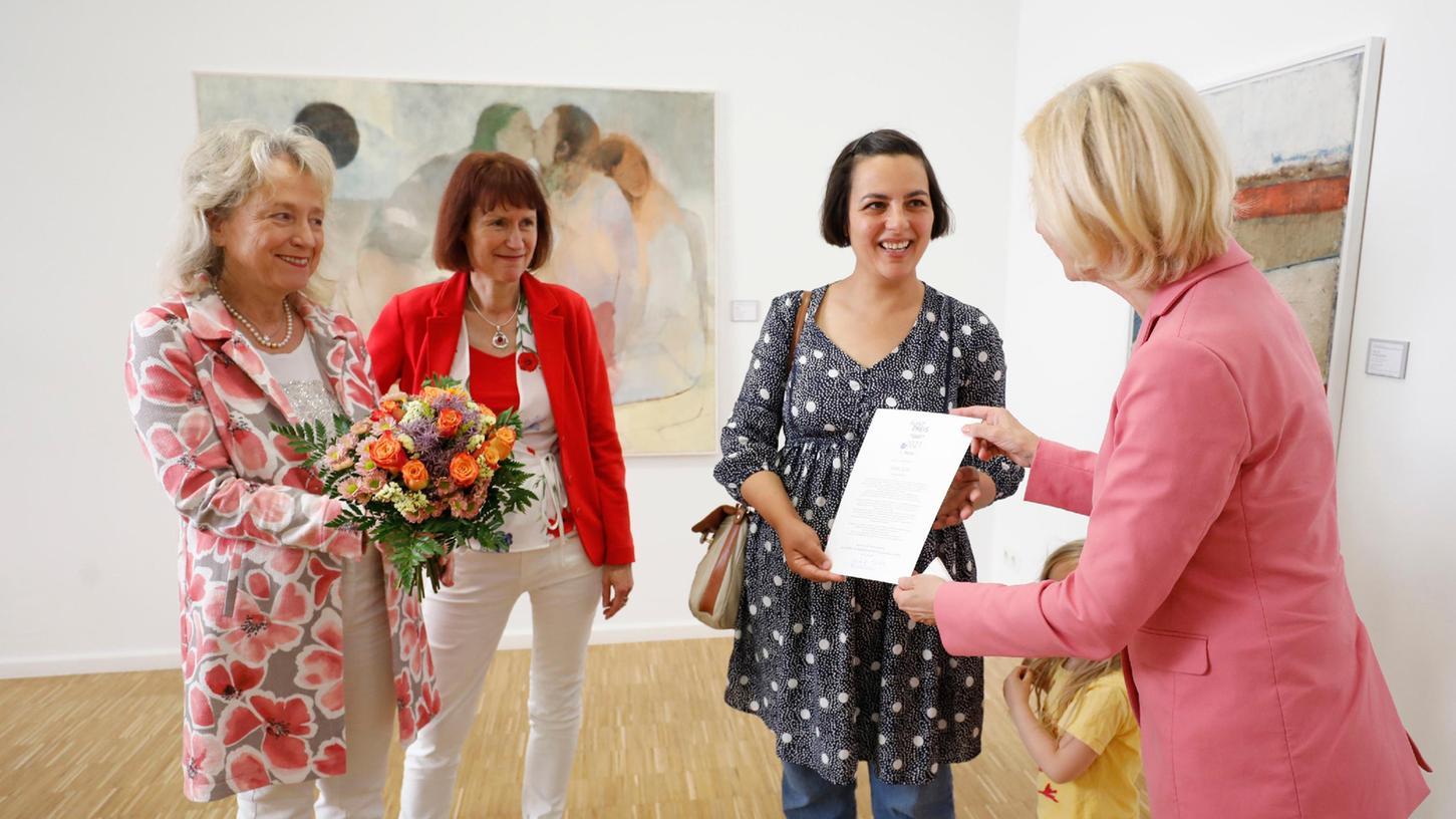 Kulturbürgermeisterin Julia Lehner (re.) übergab die Auszeichnungin Anwesenheitder beiden Verlegerinnen Bärbel Schnell (li.) und Sabine Schnell-Pleyer an die Hauptpreisträgerin Fatma Güdü, die ihre kleine Tochter mitgebracht hatte.