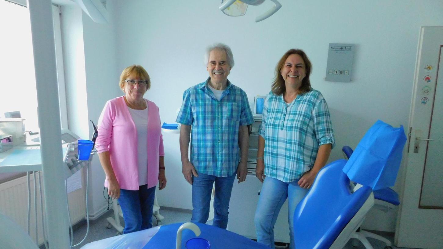 Abschiedsfoto in der Zahnarztpraxis: Im Bild von links gesehen Assistentin Maria Frohnhöfer, in der Mitte Arno Regn und rechts seine Frau Karin Regn, die ebenfalls in der Praxis mitgearbeitet hat.