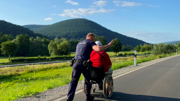 Ein Beamter schiebt den Rollstuhlfahrer zu seinem Freund.