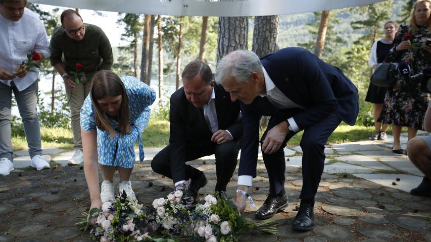 Der schwedische Ministerpräsident Stefan Löfven (M.) legt an der Gedenkstätte auf der Insel Blumen nieder.