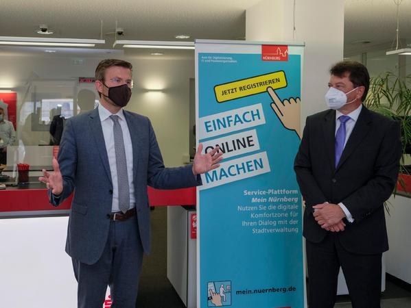 Oberbürgermeister Marcus König (links) und Sparkassen-Vorstandsmitglied Matthias Benk (rechts) stellen dieBürgerservices in der Sparkassen-Geschäftsstelle Mögeldorf vor.