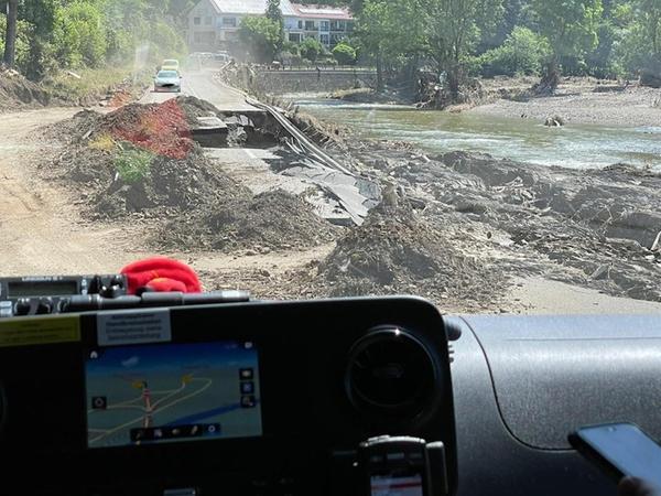 Von einem intakten Straßennetz kann vielerorts nicht mehr die Rede sein. Hier wird ein Loch in der Straße, das das Hochwasser gerissen hat, notdürftig umfahren.