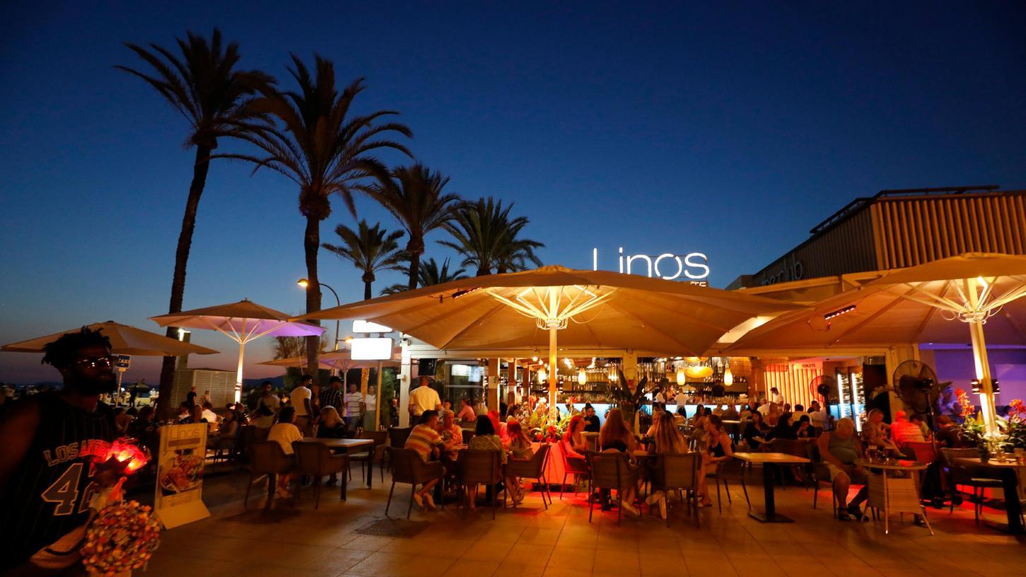Es könnte alles so schön sein: Menschen sitzen in einer Bar an der Strandpromenade von Palma de Mallorca. Doch die Zahlen der Corona-Neuinfektionen sind auf der Ferieninsel zuletzt heftig gestiegen. Deutschland erklärt ganz Spanien künftig wieder zum Hochinzidenzgebiet.