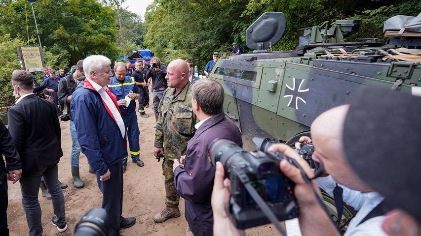 Horst Seehofer unterhält sich mit Kräften der Bundeswehr, die bei der gefährdeten Steinbachtalsperre bei Euskirchen eingesetzt sind.