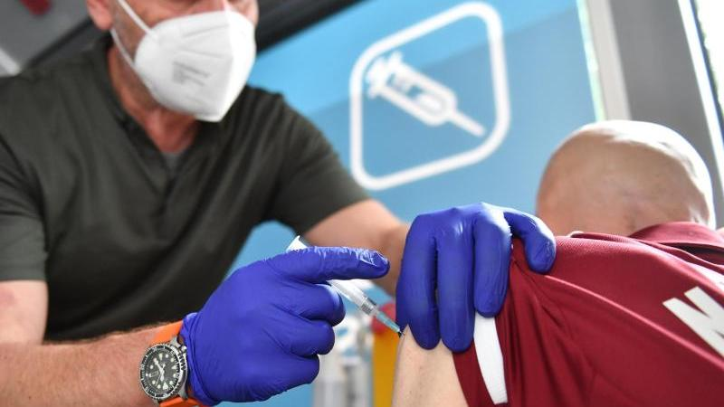 Arzt Dieter Rührig (l) impft einen Fan vom 1. FC Nürnberg vor dem Spiel gegen Erzgebirge Aue. Geimpft wird in einem Impfbus vor dem Stadion.