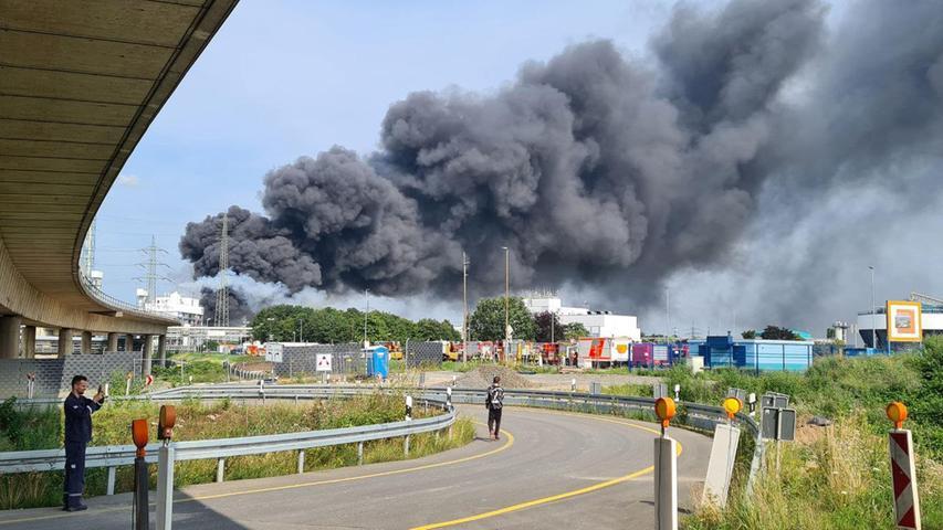 27.07.2021, Nordrhein-Westfalen, Leverkusen: Eine dunkle Rauchwolke steigt über dem Chemiepark auf. Einsatzkräfte der Werkfeuerwehr sind im Einsatz. Foto: Mirko Wolf/dpa +++ dpa-Bildfunk +++