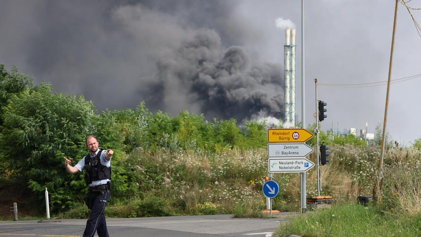 27.07.2021, Nordrhein-Westfalen, Leverkusen: Ein Polizist steht unweit einer Zufahrt zum Chempark über dem eine dunkle Rauchwolke aufsteigt. Nach einer Explosion seien Feuerwehr, Rettungskräfte und Polizei aktuell im Großeinsatz, erklärte die Polizei. Wegen der Schadenslage ist die viel befahrende Autobahn A1 bei Leverkusen gesperrt worden. Foto: Oliver Berg/dpa +++ dpa-Bildfunk +++