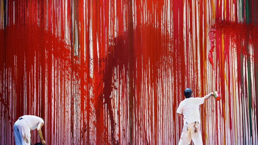 Zu Wotans Feuerzauber werden rote Farbfontänen gegen die Wand geschleudert.