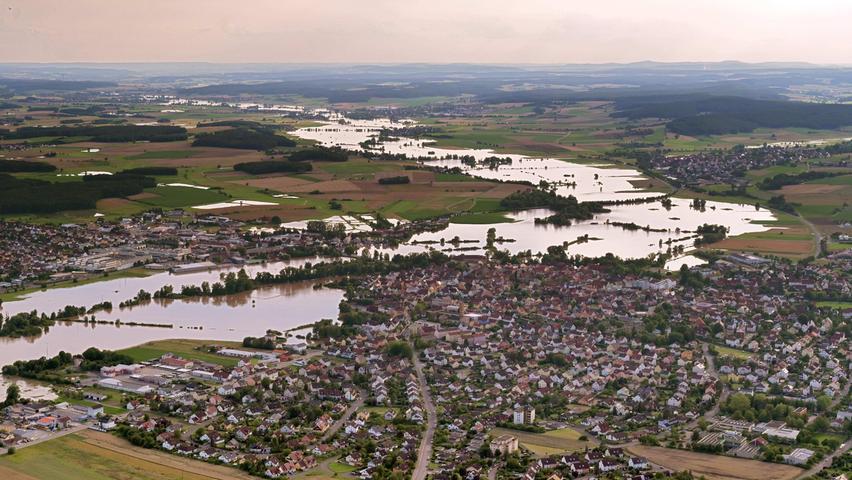 Das Aisch-Hochwasser vom Wochenende um den 10. Juli 2021 war ein Jahrhundert-Hochwasser, an manchen Stellen lagen die Fluten sogar leicht über dieser Marke. Hier erstreckt sich der Blick aus der Luft in Richtung Westen auf Höchstadt/Aisch.