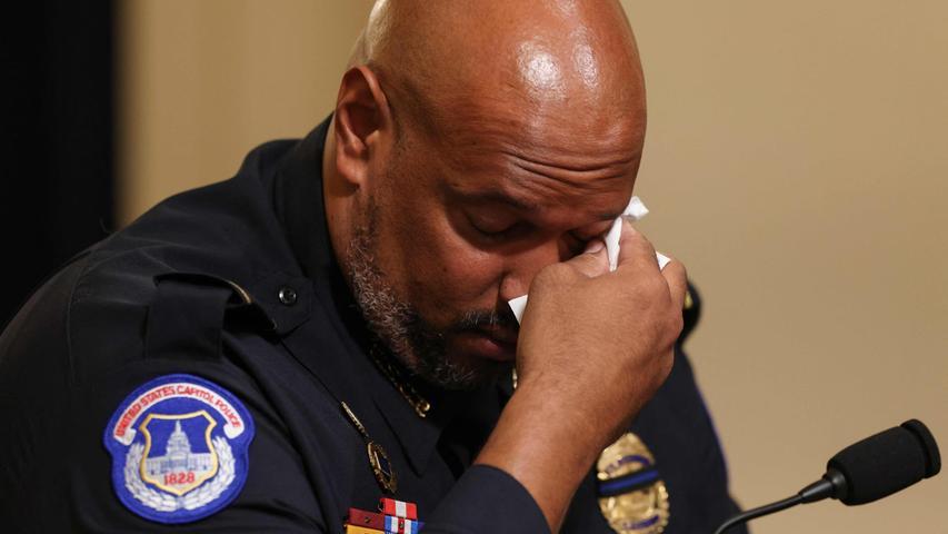 """Harry Dunn, Angehöriger der amerikanischen Kapitol-Polizei, wird von seinen Emotionen überwältigt: Bei einer Anhörung vor dem Untersuchungsausschuss zur Erstürmung des Kapitols schildert er, wie er durch den Angriff fanatischer Trump-Anhänger in Lebensgefahr geriet. Der Polizist wurde rassistisch beleidigt, ein Angreifer warf ihm einen Lautsprecher an den Kopf, ein anderer versuchte, ihm das Auge auszustechen. Als er unter den Attacken zu Boden ging, rief jemand: """"Du wirst auf den Knien sterben""""."""