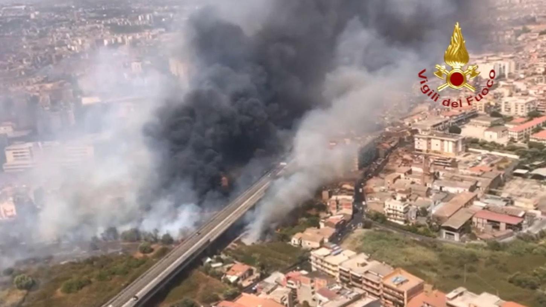 Catania: Blick aus einem Hubschrauber der Feuerwehr auf Brände neben der Via Palermo - dichter Rauch zieht über die Wohnhäuser. In Italien sind die Feuerwehren weiter im Dauereinsatz gegen die lodernden Waldbrände. Allein in Sizilien rückten die Retter 250 Mal aus.