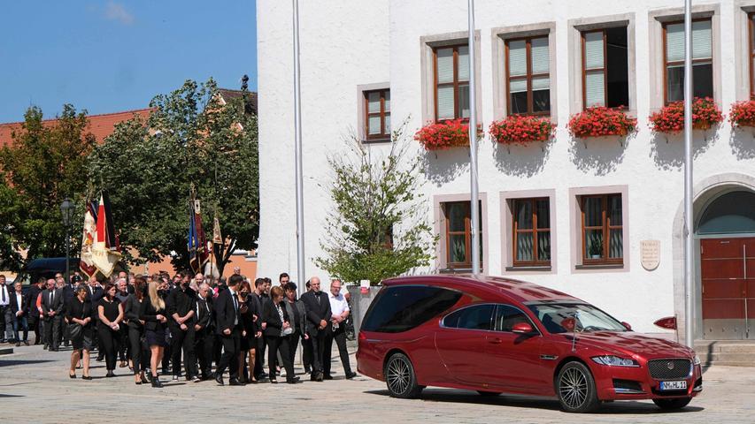 Die Trauergäste schritten hinter dem Leichenwagen am Rathaus vorbei.