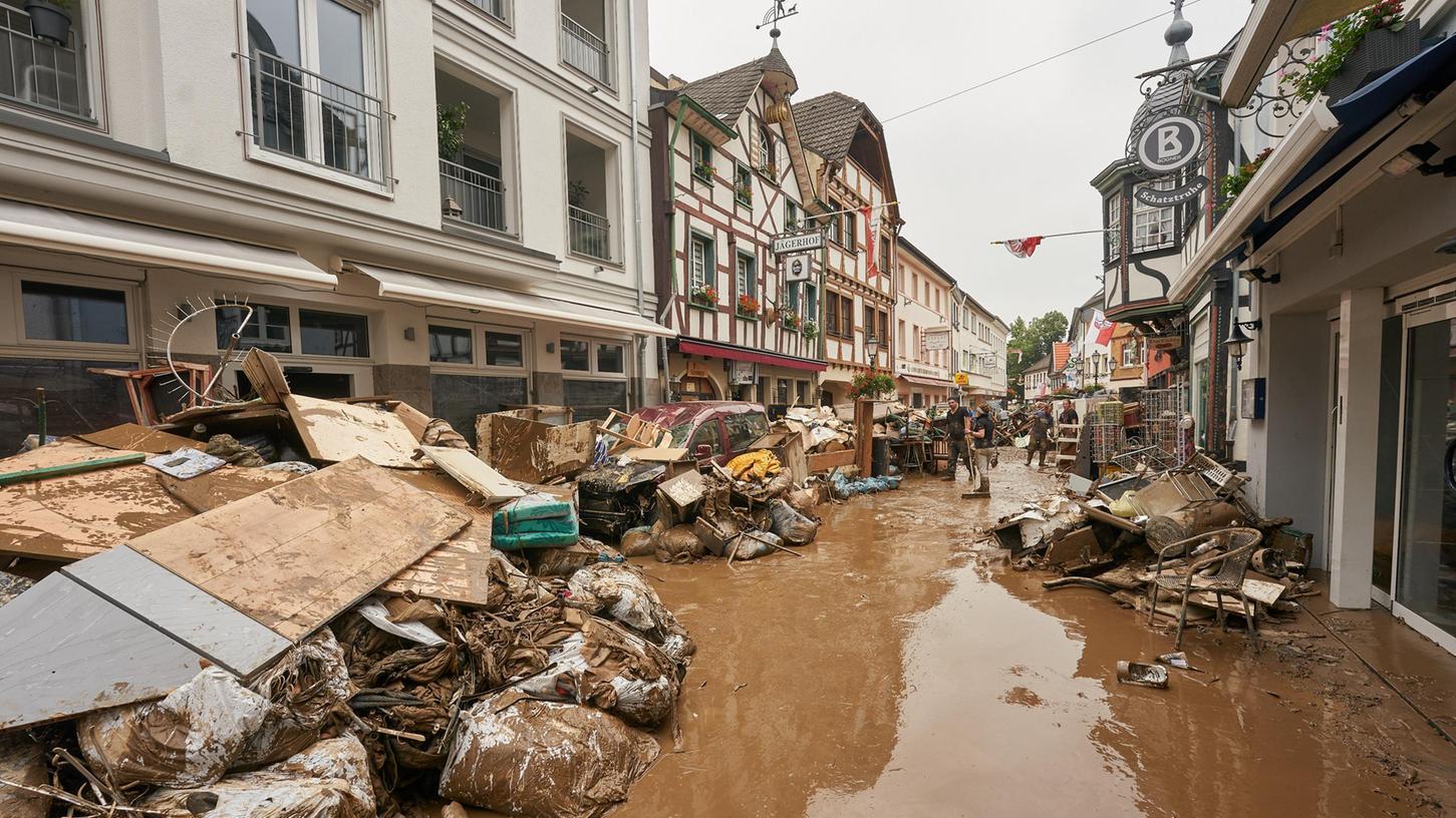 Anwohner und Ladeninhaber versuchen, nach der verheerenden Hochwassernacht ihre Häuser vom Schlamm zu befreien und unbrauchbares Mobiliar nach draußen zu bringen.