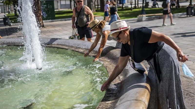 Menschen erfrischen sich bei Temperaturen über 40 Grad mit Wasser aus einem Brunnen auf dem Syntagma-Platz in Athen