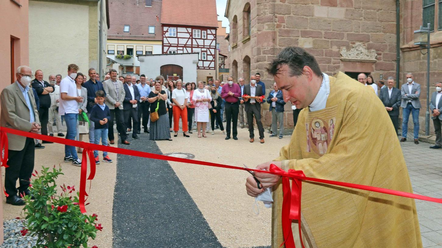 Pfarrer Sebastian Lesch hatte beim Umbau des Hauses selbst mit Hand angelegt und durfte sich nun einreihen, um das rote Eröffnungsband zu durchschneiden.