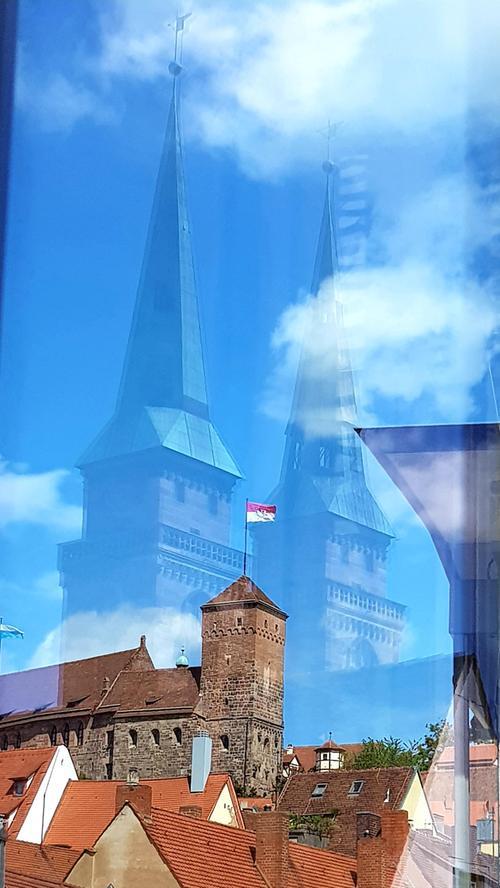 Die Sebalduskirche scheint über der Nürnberger Burg zu schweben. Fotografiert mittels Fensterspiegelung vom Haus Eckstein.