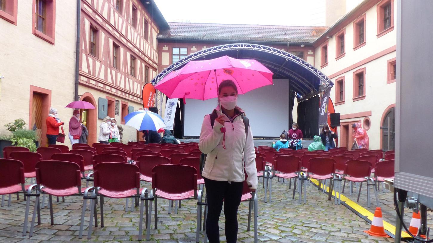 Annalena aus Heroldsbach, ausgerüstet mit Schirm und Maske, freut sich trotz des widrigen Wetters auf den Kino-Abend.