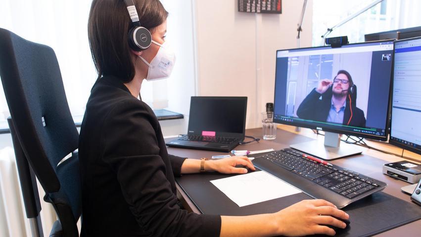 Die Mitarbeiterin einesdigitalen Corona-Schnelltestzentrumskontrolliert den Test eines Patienten am Bildschirm und schickt ihm dann bei negativem Ergebnis ein pdf-Zertifikat.