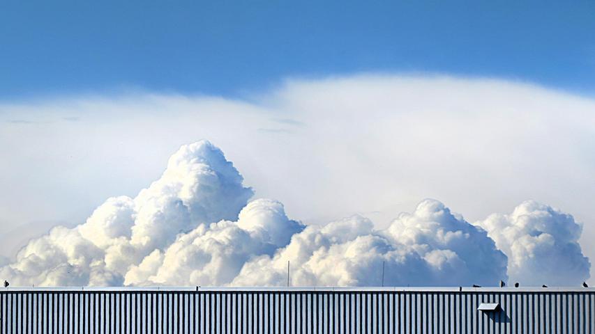 Wie Sahnehäubchen erhebt sich ein Wolkengebirge über einem Hangar des Nürnberger Flughafens.