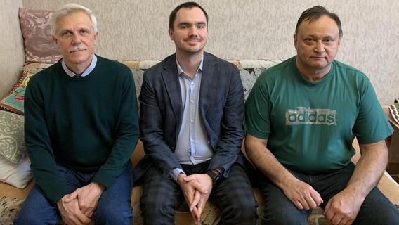 Anatoly Rassolenko vom Nürnberger IT-Unternehmen Hemmersbach sitzt zwischen Valery Bespalov (li.) und Alexey Ananenko (re.) auf einem Sofa in dessen Wohnung.