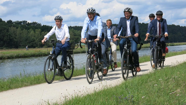 Auf Asphalt wäre es besser: Bundesverkehrsminister Andreas Scheuer (Mitte) und Vertreter der Metropolregion testen bei Baiersdorf die Strecke entlang des Kanals.