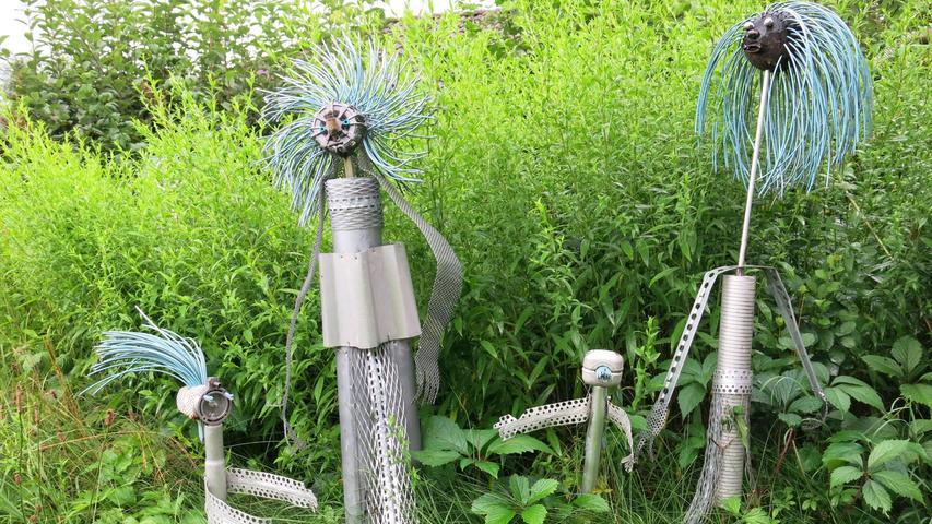 Sogar Außerirdische mit wilden Haaren aus isoliertem Draht haben ihren Platz zwischen Gräsern, Blumen und Büschen gefunden.