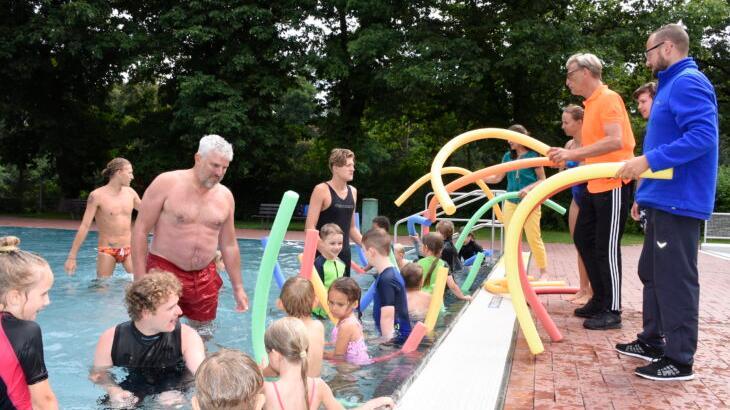 Während des Schwimmkurses im Laufer Freibad verwenden die Schüler unter anderem die Schwimmnudel als Hilfsmittel. Bürgermeister Thomas Lang (4. v. l.), Schwimmschulleiter Alexander Gallitz (3. v. r.) und Grünen-Stadträtin Erika Vogel (5. v. r.) halfen am Dienstag den Lehrern der Schwimmschule Flipper aus Burgthann.