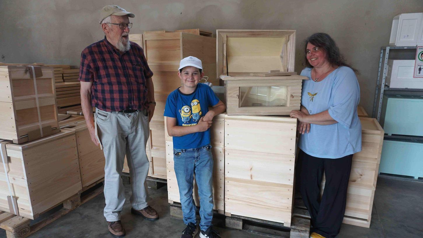 Klaus Becker mit dem Jung-Imker André und Imkerin Sandra Hack an einer Schaubeute.