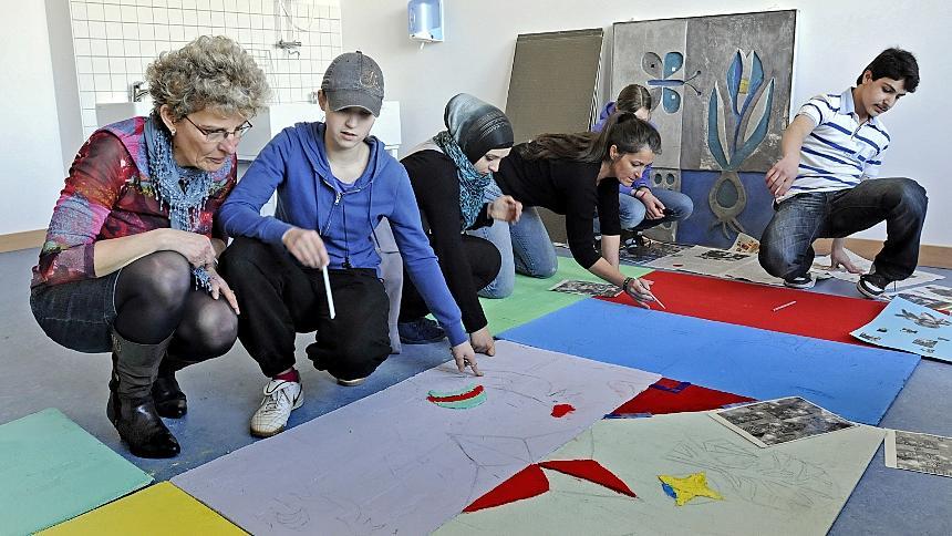 Unter Aufsicht von Lehrerin Jutta Bär (li.) und Künstlerin Manuela Dilly (3. v. re.) zeichnen die Schüler Motive auf bunte Bauplatten, die später eingespachtelt werden. Das letzte Sgrafitto-Teilstück (hinten) vom alten Schulhaus ist bereits restauriert.