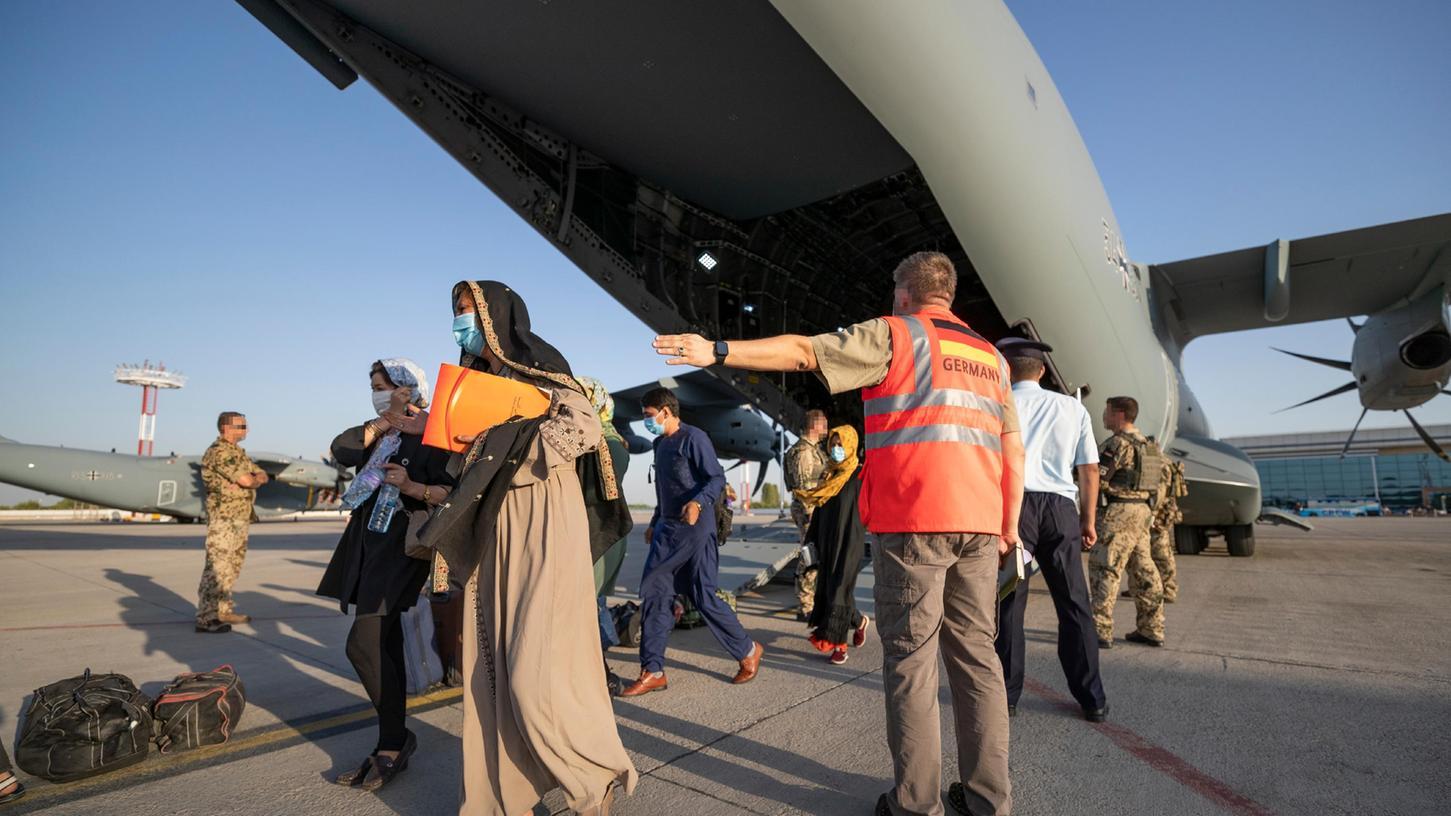 Schutzbedürftige Menschen betreten kurz nach dem Flug aus Kabul sicheren Boden zum Weiterflug nach Deutschland. Aus Afghanistan geflüchtete Personen werden nun doch nicht vorübergehend auf dem US-Truppenübungsplatz in Grafenwöhr untergebracht, die dort errichteten Notunterkünfte werden derzeit nicht benötigt.