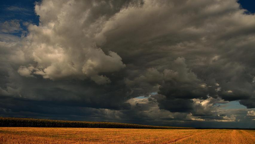 Die Sonnenstrahlen bilden einen schönen Kontrast mit den aufkommenden Regenwolken über einem abgeernteten Getreidefeld und deuten auf ein Wetterwechsel hin.
