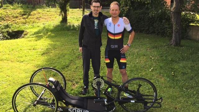Georg Knoll hat das Nationalmannschafts-Dress schon einmal übergestreift. Vor ihm das geliehene Handbike, mit dessen Hilfe er den abschließenden Marathon im Rahmen des Challenge absolvieren will. Das gesammelte Geld kommt dem krebskranken Fabian Harrer (links) zugute.