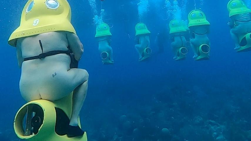 Teilnehmer der Nacktkreuzfahrt bei einer Exkursion mit Unterwasserscootern.